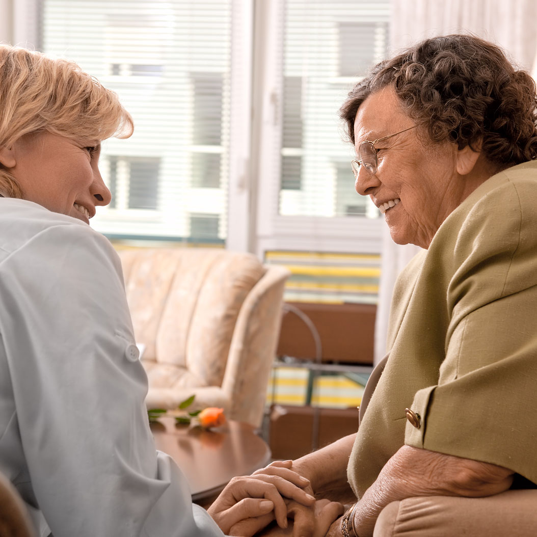 a happy senior engaging in conversation with her caregiver