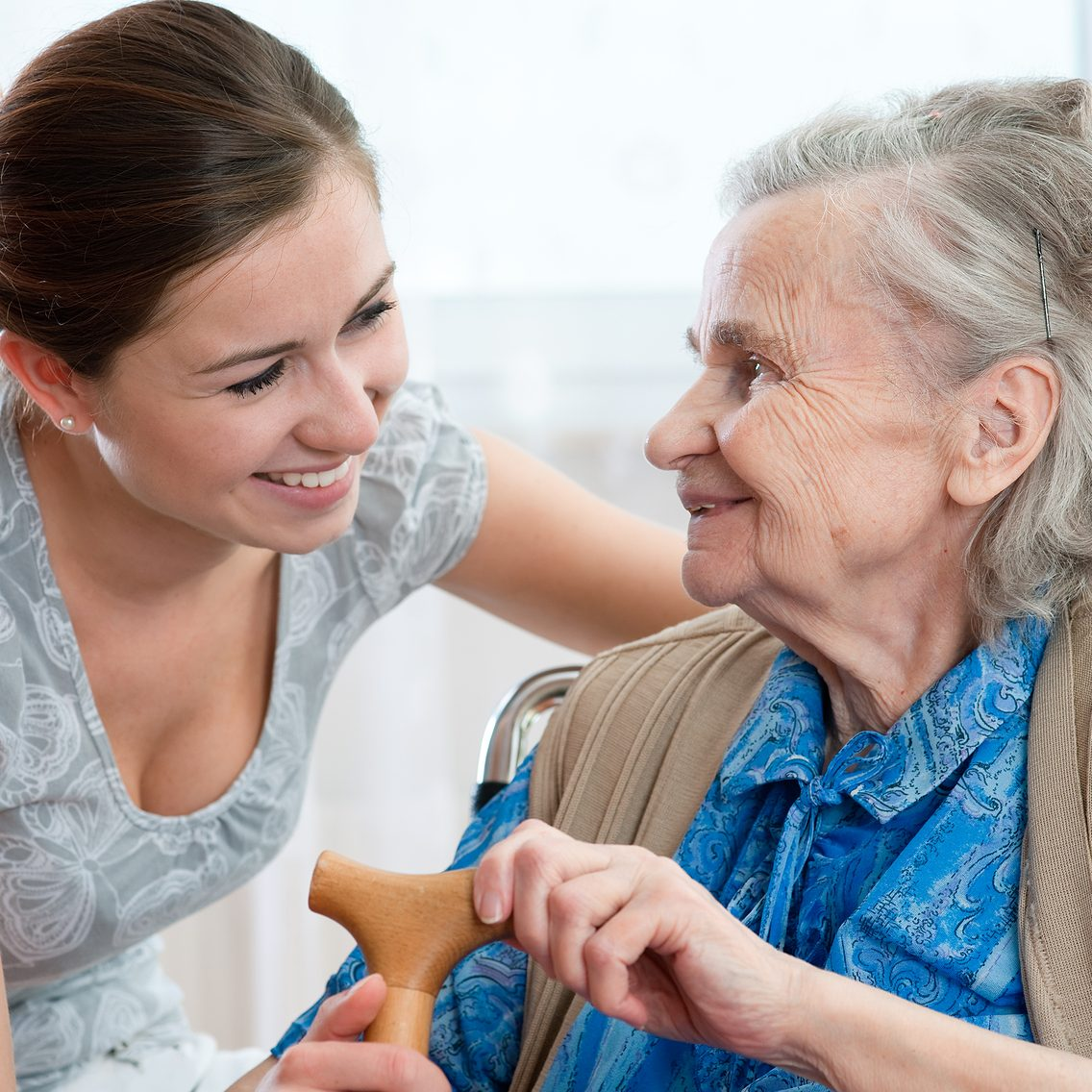 a caregiver sitting with a smiling elderly woman