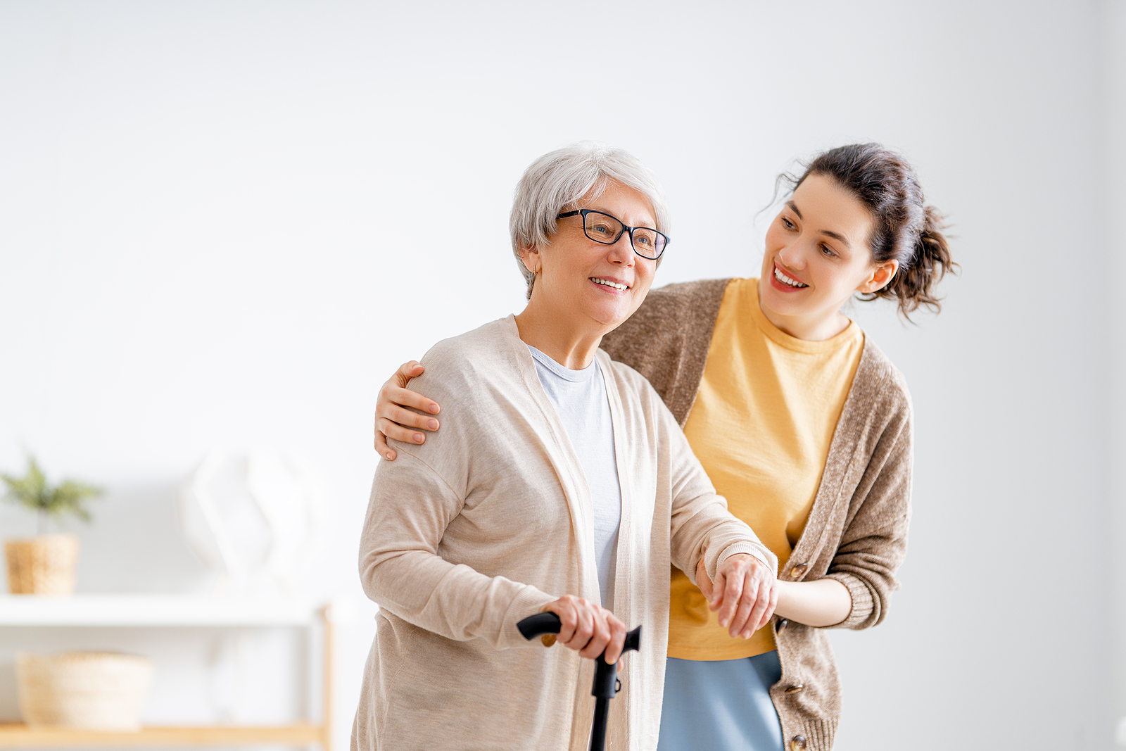 a friendly caregiver helping an elderly woman navigate her home safely