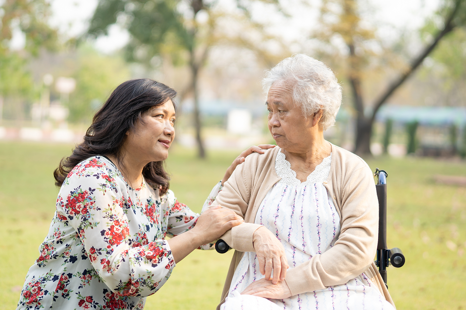 An elderly Asian woman is helped by a senior home care provider.