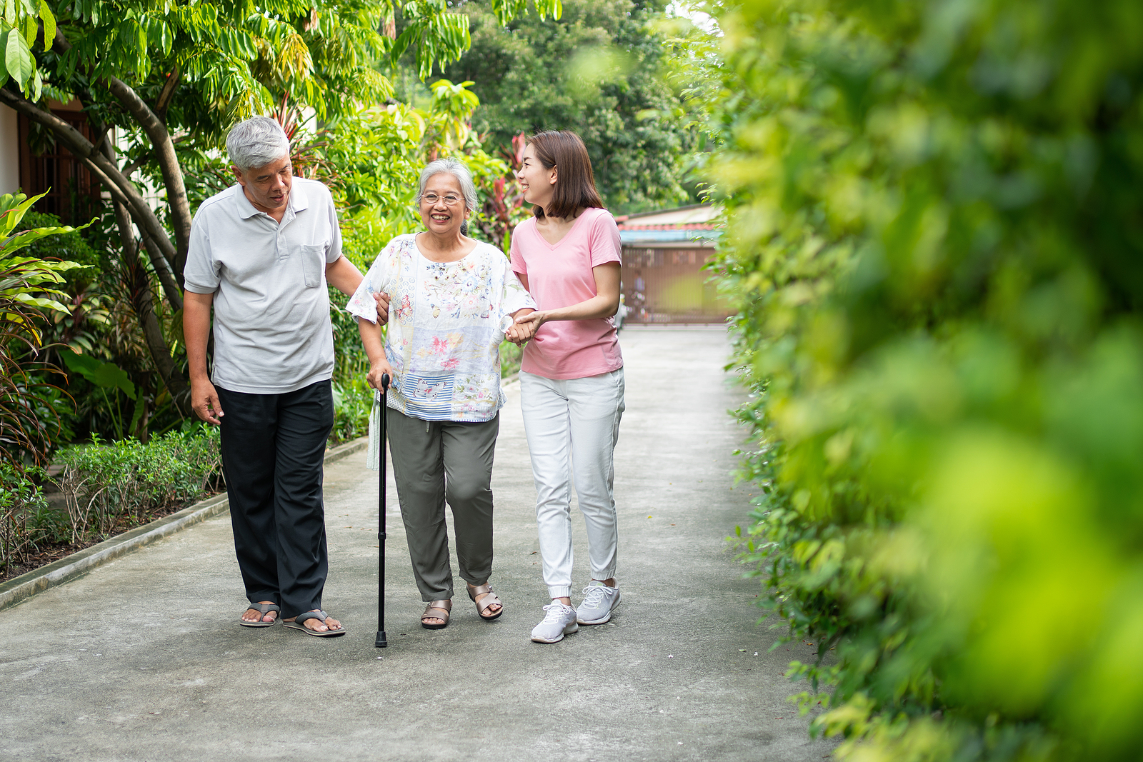 a senior woman using a cane to prevent falling as she walks along a path with family members